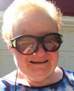 Betsey is wearing her Aira glasses with a big smile