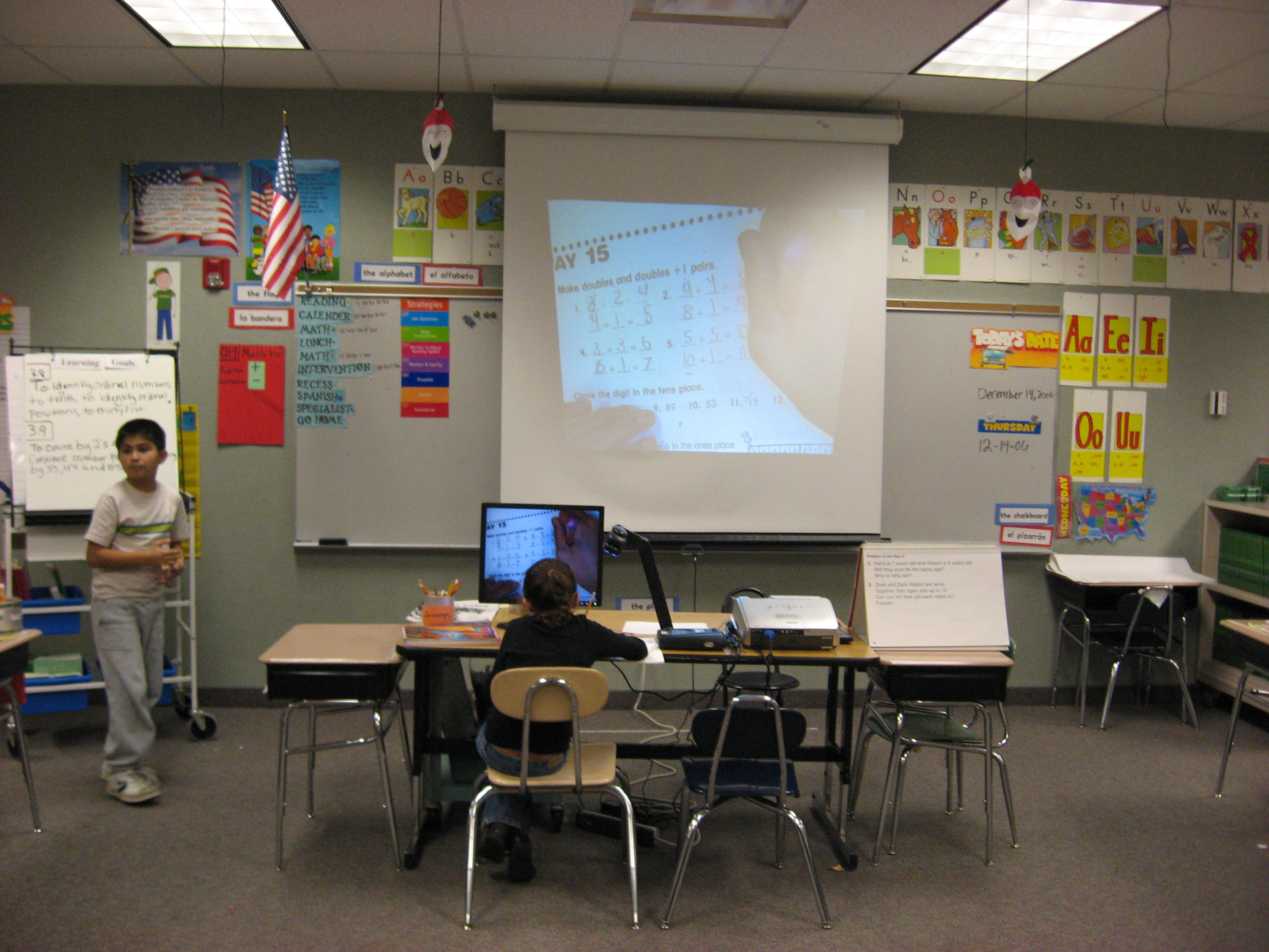 child viewing information from a monitor on her desk that sees to the front