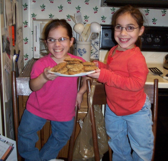 2 girls holding a plate of cookies they just made